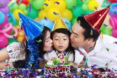 Vela del cumpleaños de la muchacha que sopla con los padres Imagen de archivo