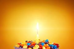 Vela del cumpleaños en la magdalena deliciosa con los caramelos Fotografía de archivo libre de regalías