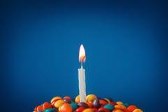 Vela del cumpleaños en la magdalena deliciosa con los caramelos Imagenes de archivo
