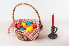 Vela del huevo de la cesta de Pascua en una palmatoria Imagenes de archivo
