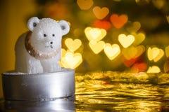 Vela del oso polar y luces de la Navidad en la forma del corazón Imagenes de archivo
