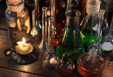 Vela del vintage con los frascos y las botellas en la tabla de la bruja Foto de archivo libre de regalías