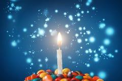 Vela do aniversário no queque delicioso com doces Foto de Stock