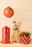 Vela do Natal com as bolas vermelhas de esqui da fita e do presente no fundo de madeira Fotografia de Stock Royalty Free
