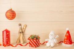 Vela do Natal com as bolas vermelhas de esqui da fita e do presente no fundo de madeira Um tampão de Santa Claus Imagem de Stock