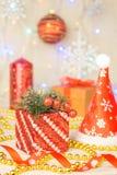 Vela do Natal com as bolas vermelhas de esqui da fita e do presente no fundo de madeira Um tampão de Santa Claus Fotos de Stock Royalty Free