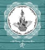 Vela do Natal no círculo no estilo da Zen-garatuja com laço no fundo de madeira azul Imagem de Stock Royalty Free