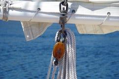 Vela do veleiro e cordas de madeira do equipamento contra o fundo da água Fotografia de Stock