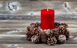 Vela e grinalda vermelhas ardentes do cone do pinho para a estação do Natal foto de stock