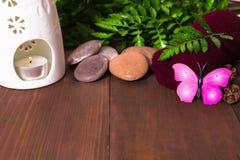 Vela en la lámpara, las piedras y la toalla del aroma adornadas con el helecho y p Fotos de archivo libres de regalías
