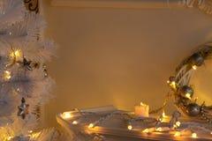 Vela, festão, grinalda em uma prateleira da chaminé e ramos da árvore do White Christmas à vista das luzes fotos de stock royalty free