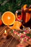 A vela, fruto alaranjado, maçã, varas de canela próximo ferventou com especiarias o vinho no fundo de madeira Decoração do Natal  Fotos de Stock