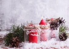 Vela, galhos e cones vermelhos em um fundo de madeira coberto de neve Foto de Stock Royalty Free