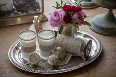 A vela ilumina rosas em uma placa de prata Imagem de Stock
