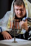 A vela judaica ilumina a mão masculina que leve velas no menorah fotografia de stock royalty free