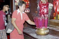 Vela madurada de la luz de la mujer y palillo de ídolo chino a rogar para los parientes salidos en templo chino en Manila Imágenes de archivo libres de regalías