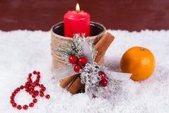 Vela, mandarinas y decoración rojas de la Navidad en la nieve Fotografía de archivo