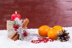 Vela, mandarinas y decoración rojas de la Navidad en la nieve Imágenes de archivo libres de regalías