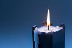 Vela negra con la mecha ardiente en fondo azul marino de la pendiente Copie el espacio imágenes de archivo libres de regalías