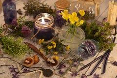 Vela negra, flores, hierbas curativas y objetos místicos en los tablones Foto de archivo libre de regalías