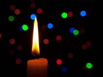 Vela no fundo preto com luzes coloridas, atmosfera do Natal Imagens de Stock Royalty Free