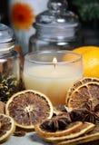 Vela, palillos de cinamomo y naranja seca Foto de archivo libre de regalías
