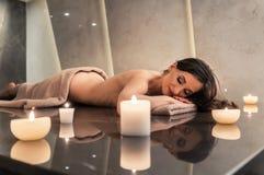 Vela perfumada al lado de la mujer joven en la tabla de mármol del masaje en el SP Fotografía de archivo