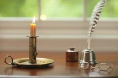 Vela, pluma de canilla y vidrios coloniales en el escritorio con la ventana Foto de archivo