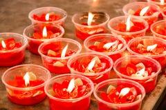Vela roja ardiente de la flor en la capilla china para hacer mérito adentro Fotografía de archivo libre de regalías