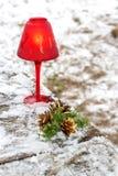 Vela roja de la Navidad con las ramas y los conos del abeto en invierno Fotos de archivo libres de regalías