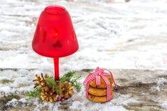 Vela roja de la Navidad con las ramas y los conos del abeto en invierno Foto de archivo