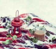 Vela roja festiva en linterna y la taza de café en la manta con nieve Imagenes de archivo