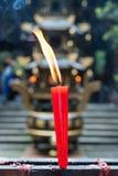 Vela roja que quema en un templo budista Fotografía de archivo