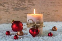 Vela romántica de la Navidad con la decoración roja del corazón Foto de archivo libre de regalías