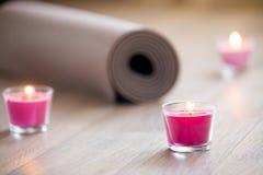 Vela rosada encendida y yoga marrón rodada, estera de los pilates en la Florida Fotos de archivo
