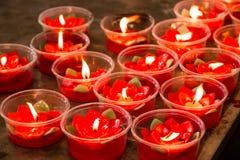 Vela vermelha ardente da flor no santuário chinês para fazer o mérito dentro Fotografia de Stock