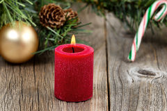 Vela vermelha ardente do Natal com sempre-verde e ornamento em rus foto de stock