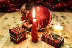 A vela vermelha iluminou-se ao lado de alguns pacotes dos presentes e de uma bola vermelha do ornamento do Natal fotografia de stock