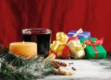 Vela, vino reflexionado sobre y regalos de la Navidad Fotos de archivo libres de regalías