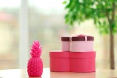 Vela y cajas elegantes de la piña en la tabla dentro Imágenes de archivo libres de regalías
