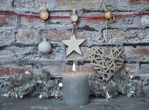 Vela y decoración ardientes de la Navidad delante de la pared de ladrillo Fotografía de archivo libre de regalías