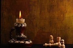 Vela y pedazos de ajedrez antiguos Imagen de archivo libre de regalías
