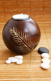 Vela y piedras en la estera de bambú Fotografía de archivo libre de regalías