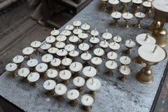 Velas alineadas en fila en monasterio en Nepal Imagenes de archivo
