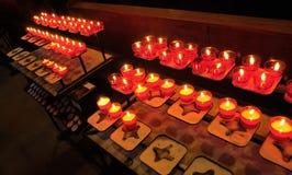 Velas amarelas de incêndio em candelabros vermelhos Imagens de Stock Royalty Free