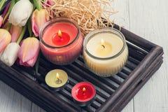 Velas amarelas e cor-de-rosa do aroma com tulipas Fotos de Stock Royalty Free