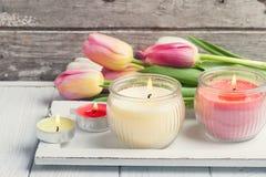 Velas amarelas e cor-de-rosa do aroma com tulipas Fotografia de Stock