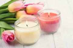 Velas amarelas e cor-de-rosa do aroma com tulipas Foto de Stock Royalty Free