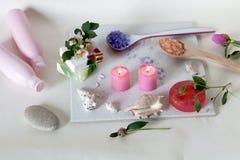 Velas ardentes cor-de-rosa, flores, escudos, sab?o, produtos do cuidado em um fundo claro foto de stock royalty free