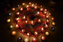 Velas ardentes decoradas no rangoli colorido Fotos de Stock Royalty Free